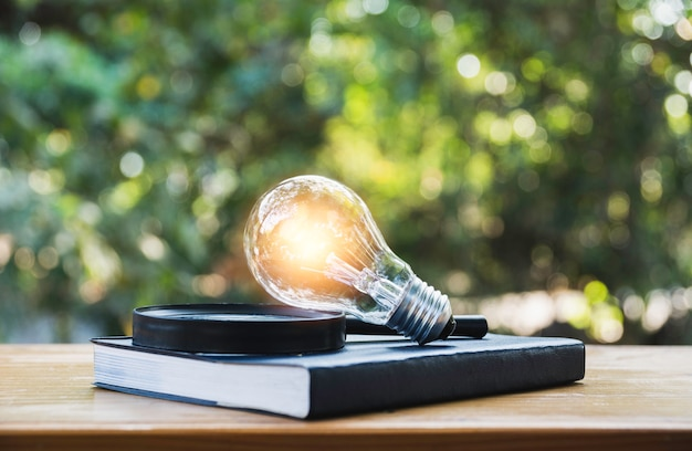 Light bulb and a book on table Premium Photo