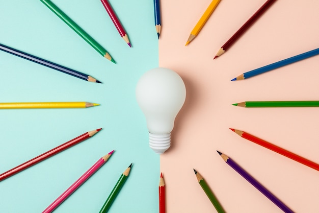 Light bulb and colored pencil on blue and pink background Premium Photo
