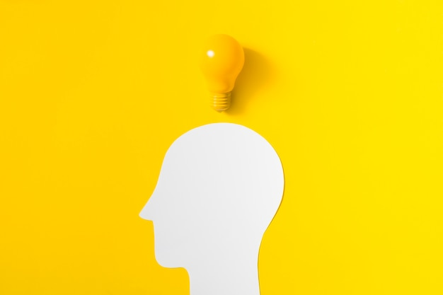 Light bulb over the cut out white human head on yellow background Free Photo