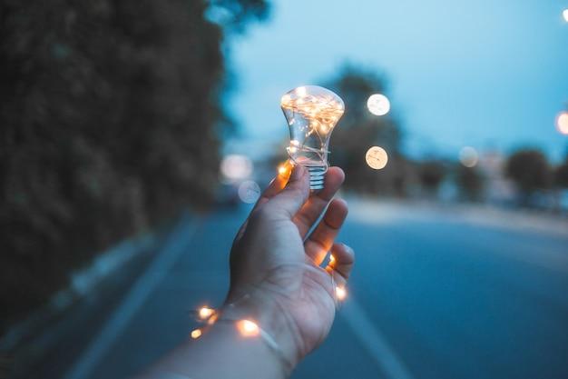 Light bulb fantazy, light bulb in hand, light bulb and bokeh Premium Photo