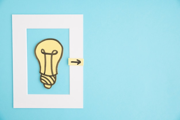 Light bulb frame with directional arrow on blue background Free Photo
