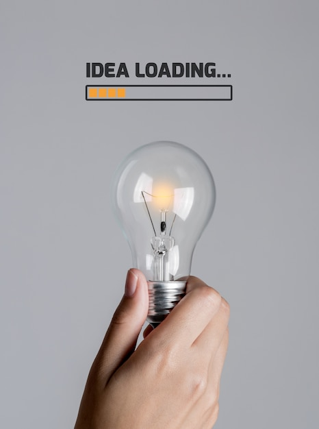 Light bulb gradually starts turn on in woman hand with text Premium Photo