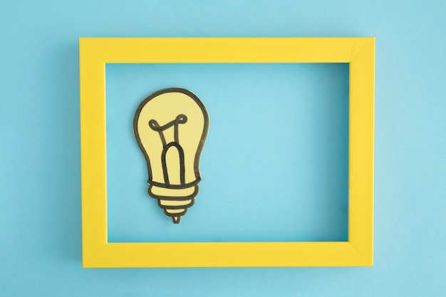 Light bulb paper cutout in the yellow border frame on blue background Free Photo