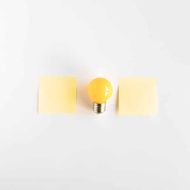Light bulb between two adhesive notes on white background Free Photo