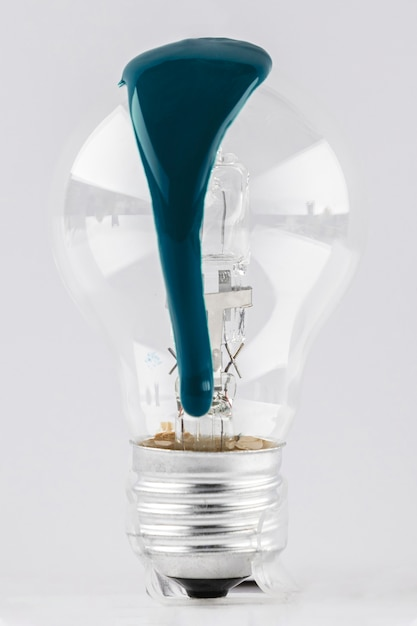 Light bulb with dripping green paint Free Photo