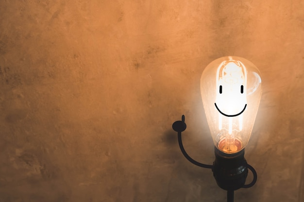 Light bulb with smile face concept on old concrete wall background. Premium Photo
