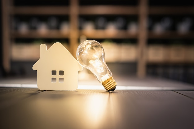 Premium Photo | Light bulb with wood house on the table