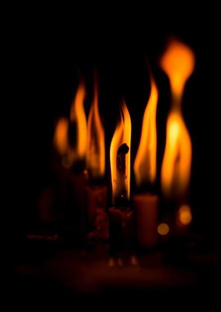 黒の背景で燃えているろうそく Premium写真