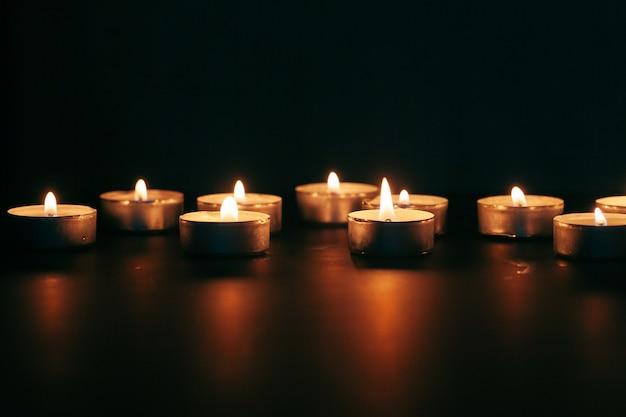 The light of the candle illuminates the darkness Premium Photo