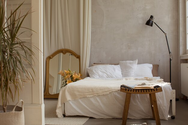 Light cozy bedroom with empty bed and coffee table with magazines copy space Premium Photo