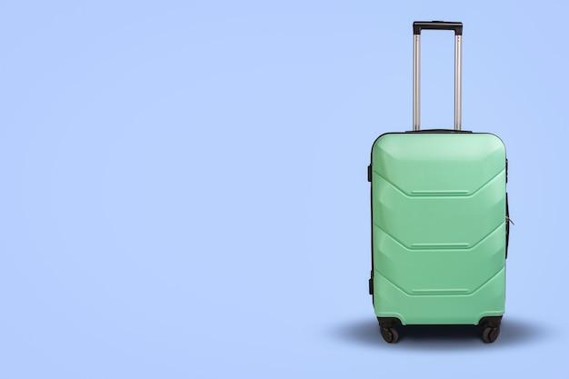 明るい青の背景に車輪の上のライトグリーンのスーツケース。旅行の概念、休暇旅行、親戚への訪問 Premium写真