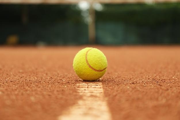 Светло-зеленый теннисный мяч на глиняном корте, крупным планом Premium Фотографии