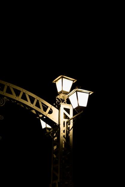 Light lamp on gate against dark background Free Photo