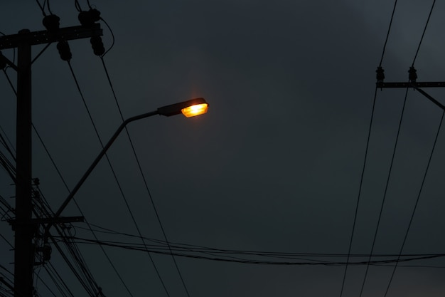 Light lamp on pole with electric wires on dark night sky background Premium Photo