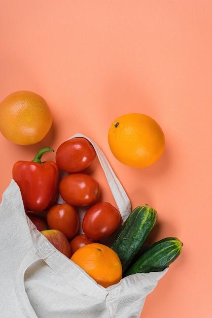 新鮮な野菜や果物が入った軽いリネンのエコバッグ。 Premium写真