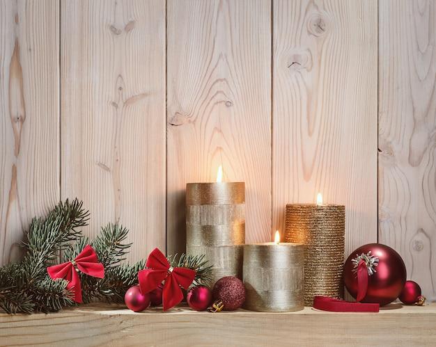 クリスマスキャンドルの光。モミの枝とお祭りのボール。 Premium写真