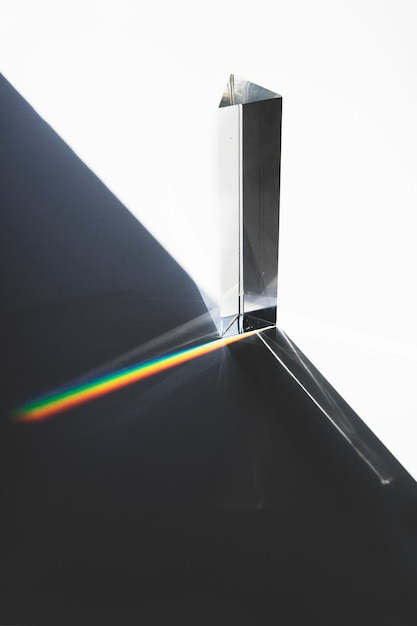 Light passing through a triangular prism with dark shadow on white surface Free Photo