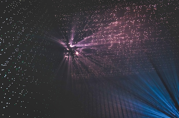 Light rays through small holes in a dark metal space Premium Photo