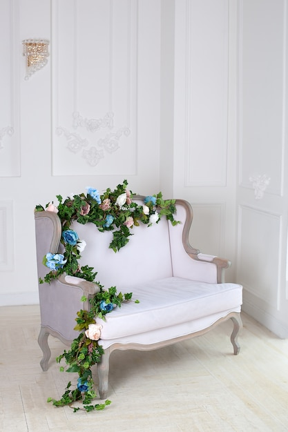 Light textile classic sofa in a vintage room. a light classic royal interior with a soft sofa with a fabric upholstery. elegant royal luxury interior with white walls and gray sofa. relaxation Premium Photo