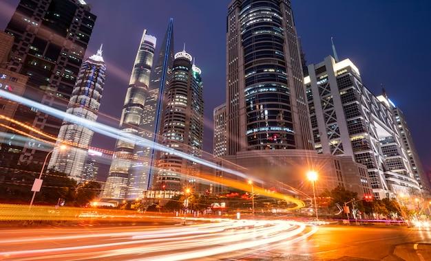 Light trails throught modern buildings Premium Photo