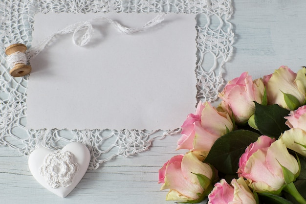On a light wooden background a sheet of paper, pink roses, a heart, rose petals Premium Photo