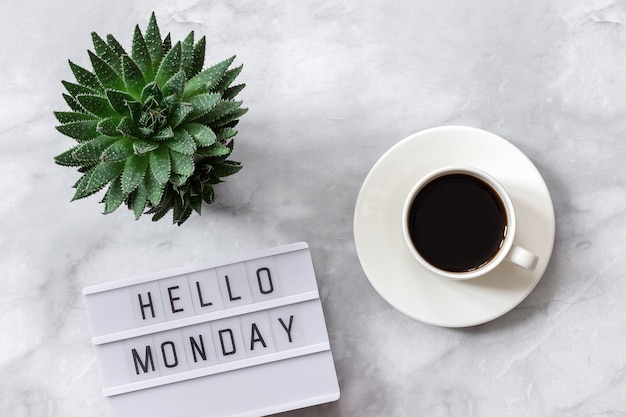 Lightbox text hello monday, cup of coffee, succulent on marble background Premium Photo