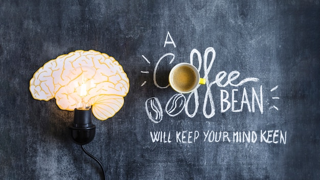 Lighted brain light bulb with text on chalkboard Free Photo