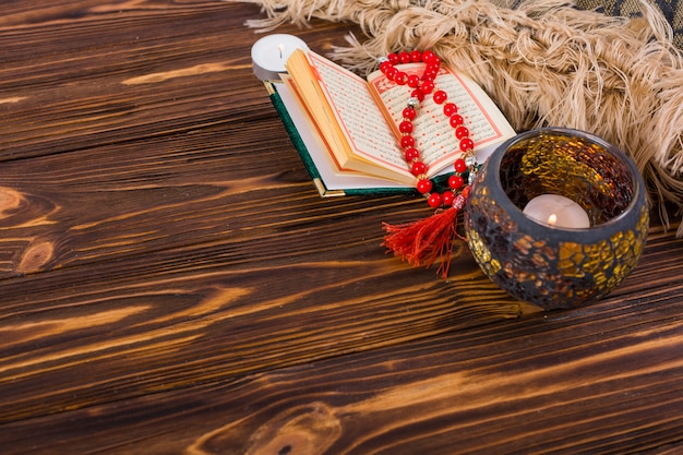 Lighted candle holder; kuran and red prayer beads on wooden desk Free Photo