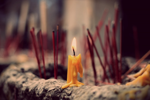 The lighted candle on joss stick pot, selected focus on the candle Premium Photo