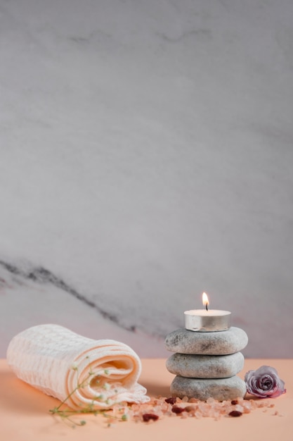 Lighted candle over the spa stones with napkin; rose and himalayan salts on peach colored backdrop against grey background Free Photo