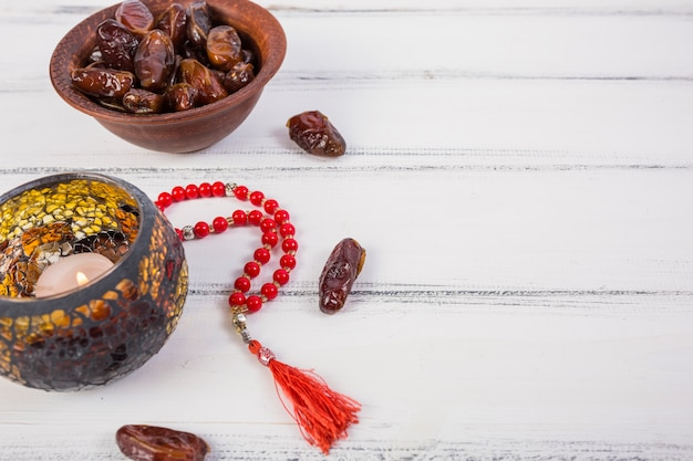 Lighted candle with bowl of juicy dates and red prayer beads on white wooden background Free Photo