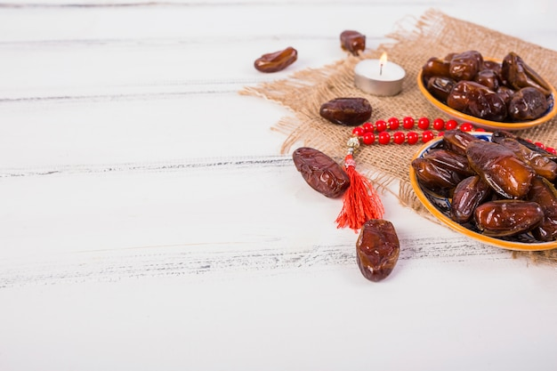 Lighted candle with plate of juicy dates and red prayer beads on wooden desk Free Photo