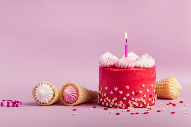 Lighted number one candle on delicious red cake with star sprinkles and waffle cones against purple backdrop Free Photo