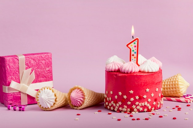 Lighted number one candle on delicious red cake with star sprinkles; waffle cones and gift box against purple backdrop Free Photo