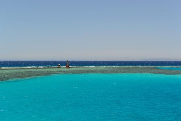 Lighthouse on the horizon of the blue sea Premium Photo
