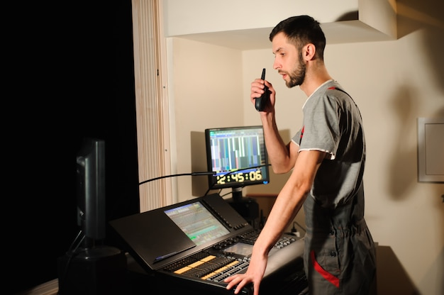 A lighting engineer works with lights technicians control on the concert show. professional light mixer, mixing console. equipment for concerts. Premium Photo