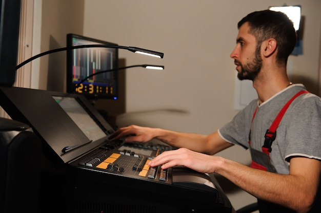 A lighting engineer works with lights technicians control on the concert show. professional light mixer, mixing console. equipment for concerts Premium Photo