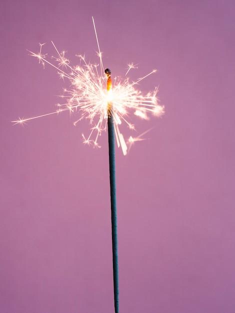 Lighting sparkler on pink background Free Photo