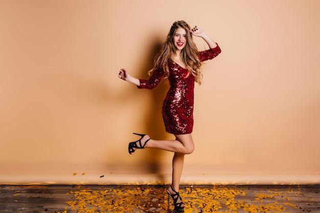 검은 우아한 샌들에 가볍게 무두질 한 아가씨 재미있는 춤과 새해 파티에 웃고 무료 사진