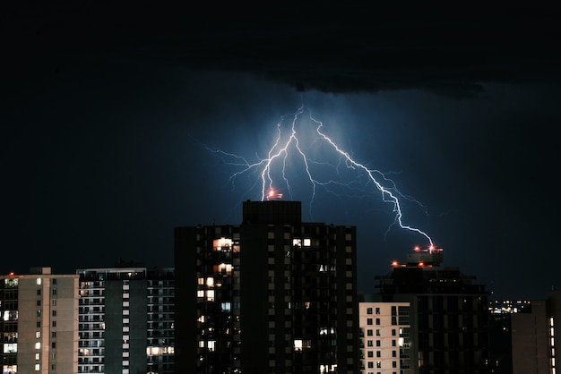 Lightning in the dark sky over the buildings in the city at night Free Photo