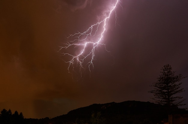 Lightning in the night sky and mountains with trees Free Photo