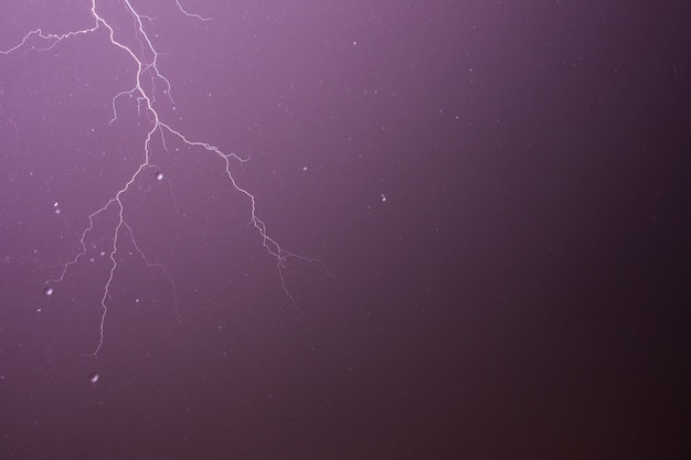 Lightning and thunderstorm on purple sky background with raindrops. Premium Photo