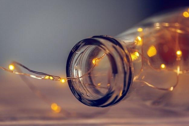 Lights garland in a glass bottle on a dark background Premium Photo
