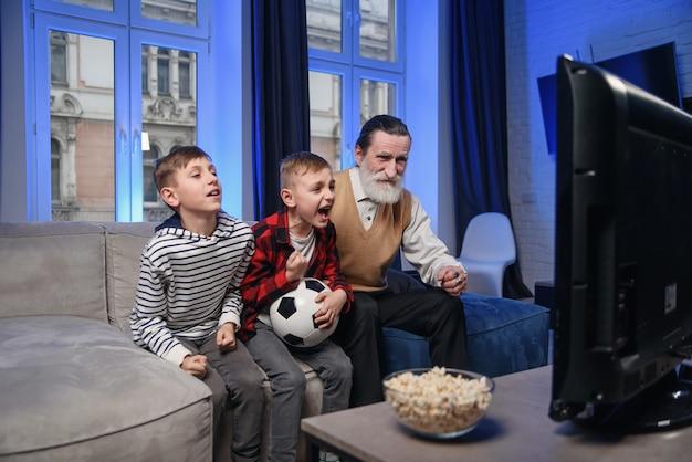 Симпатичный концентрированный старший бородатый дедушка с его веселыми внуками 10-15 лет, проводящими свое свободное время на пересмотре баскетбольного матча по телевизору Premium Фотографии