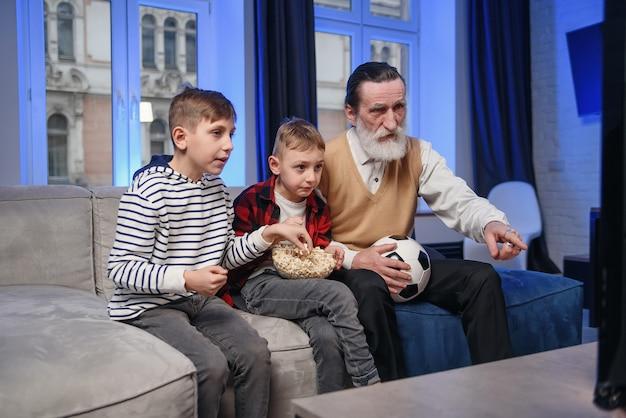 Симпатичный концентрированный старший бородатый дедушка со своими веселыми внуками, проводящими свое свободное время на пересмотре баскетбольного матча по телевизору Premium Фотографии