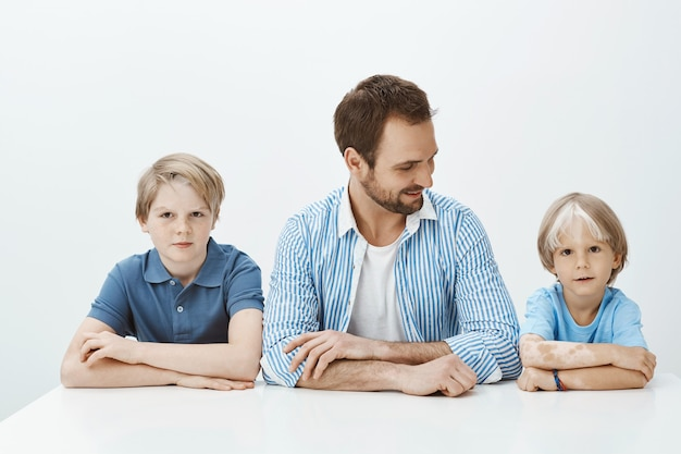 Как отец, как сыновья. портрет красивой счастливой семьи, сидящей вместе руками Бесплатные Фотографии