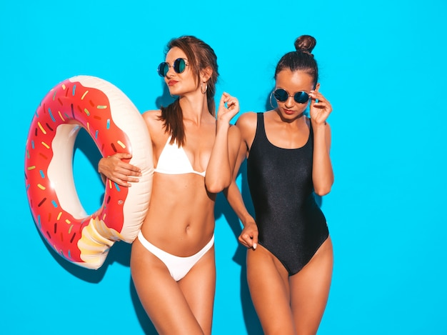 Две красивые сексуальные улыбающиеся женщины в летних белых и черных купальных костюмах. девушки в солнцезащитные очки. позитивные модели с удовольствием надувной матрас пончик lilo.изолированные на синей стене Бесплатные Фотографии