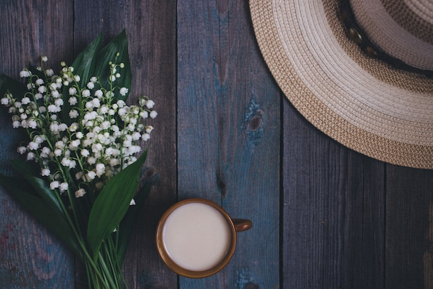 Lily of the valley bouquet, cup of coffee, tea, milk, on wooden background Premium Photo