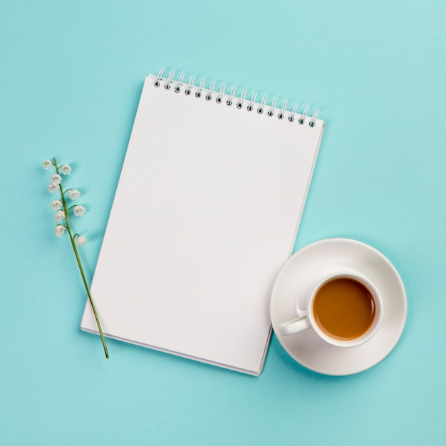 Lily of the valley flower twig on white spiral notepad with coffee cup on blue backdrop Free Photo
