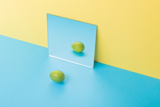 Lime on blue table isolated on yellow near mirror Free Photo